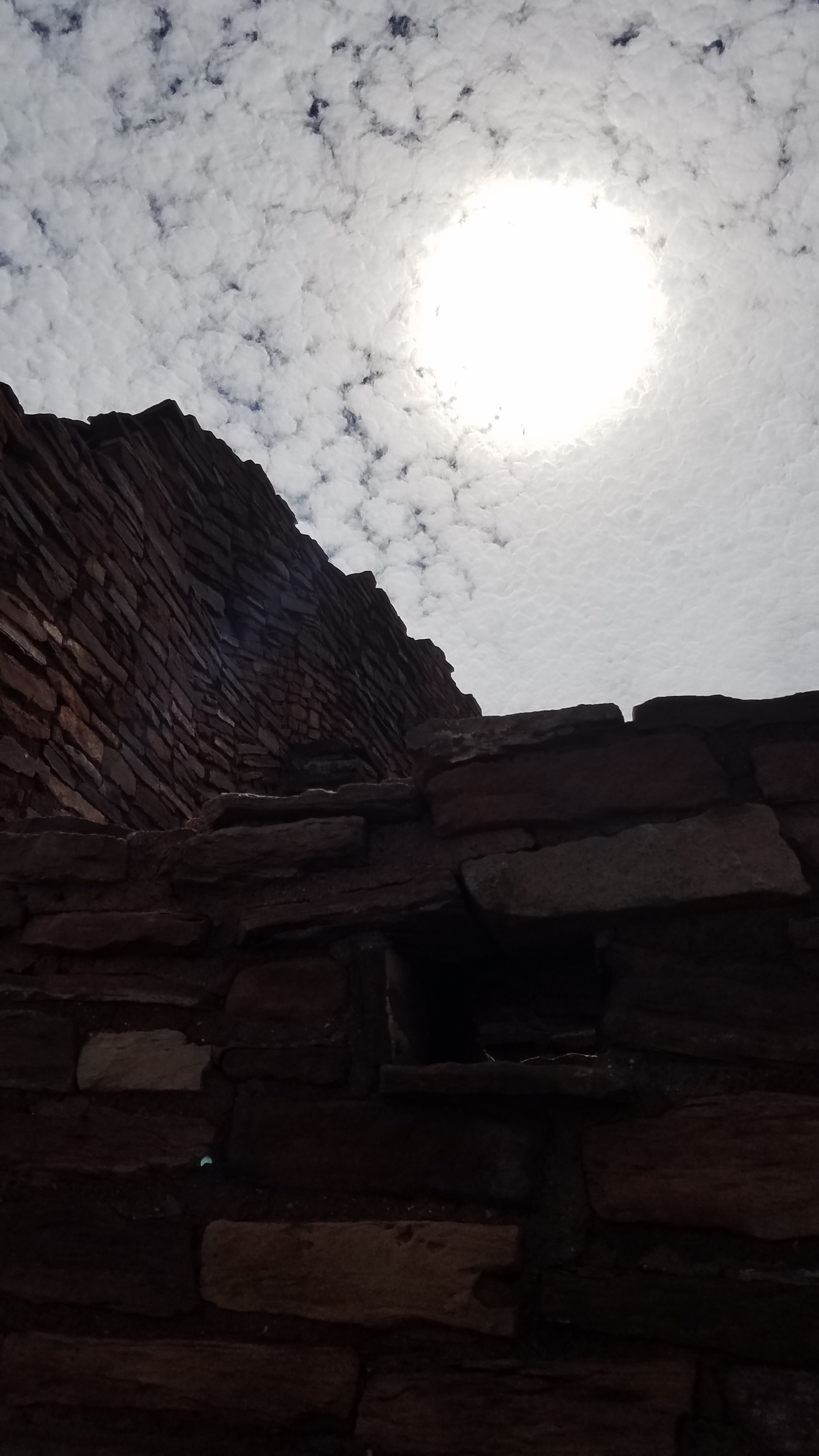 Eclipsing Sun Obscured by Clouds Beneath Wupatki Ruin